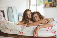 Couple relaxing together on bed - CAIF03116