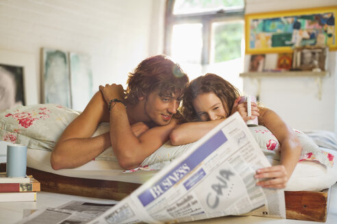 Couple reading newspaper together in bed - CAIF03119