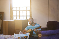 Man playing guitar in new home - CAIF03152