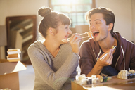 Couple eating sushi together in new home - CAIF03155