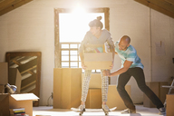 Couple unpacking boxes in new home - CAIF03158