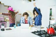 Women dancing around man in kitchen - CAIF03185