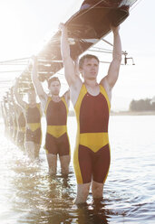 Rowing team carrying boat overhead on lake - CAIF03230