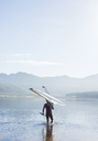 Man carrying rowing scull into lake - CAIF03236