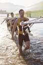 Rowing team carrying scull in lake - CAIF03248