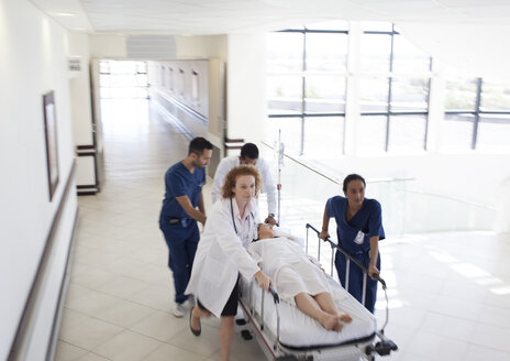 Hospital staff rushing patient to hospital room - CAIF03272