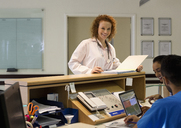Hospital staff talking at front desk - CAIF03281
