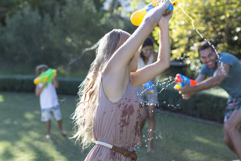 Family playing with water guns in backyard - CAIF03308