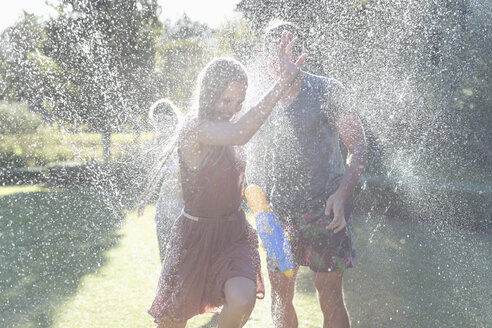 Couple playing in sprinkler in backyard - CAIF03311