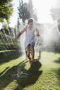 Boy playing in sprinkler in backyard - CAIF03317