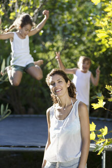 Mother standing by children on trampoline - CAIF03320