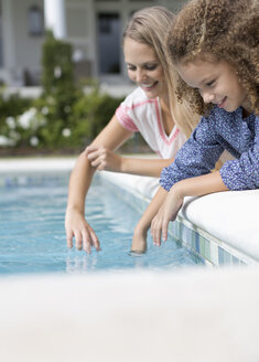 Mother and daughter dipping fingers in swimming pool - CAIF03344