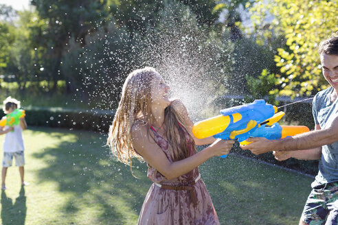 Couple playing with water guns in backyard - CAIF03350