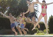 Family jumping into swimming pool - CAIF03356