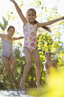 Children jumping on trampoline outdoors - CAIF03362