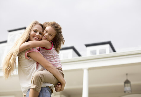 Mother and daughter hugging outside house - CAIF03380