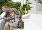 Older man and grandson petting cat on steps - CAIF03398