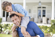 Father and son playing outside house - CAIF03401