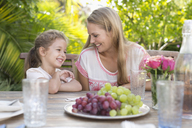 Mother and daughter smiling at table outdoors - CAIF03404