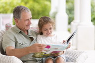 Older man reading to granddaughter on porch - CAIF03419