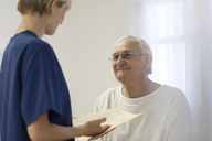 Nurse talking to older patient in hospital room - CAIF03434