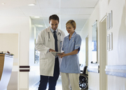 Doctor and nurse using tablet computer in hospital hallway - CAIF03446
