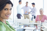 Businesswoman smiling in meeting - CAIF03473