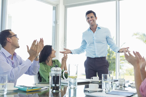 Business people cheering in meeting - CAIF03506