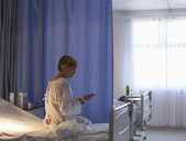 Patient using cell phone in hospital bed - CAIF03512
