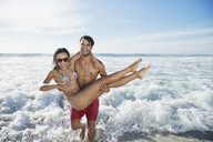 Enthusiastic man carrying woman on beach - CAIF03545
