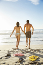 Couple holding hands and walking toward ocean on beach - CAIF03560