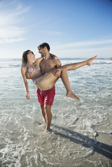 Man carrying woman in ocean surf - CAIF03566