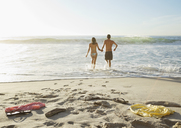 Couple holding hands and wading in ocean - CAIF03569
