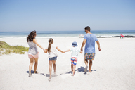 Family holding hands and walking on beach - CAIF03575