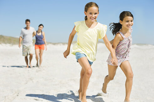 Girls holding hands and running on beach - CAIF03578