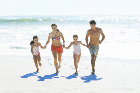 Family holding hands and running on beach - CAIF03608