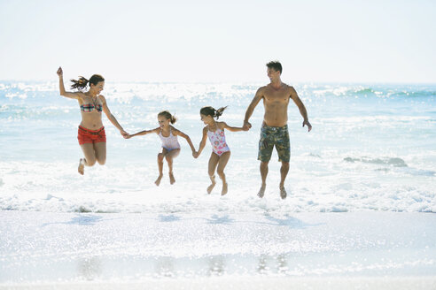 Family jumping in waves on beach - CAIF03611