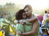 Couple in sleeping bag hugging outside tents at music festival - CAIF03632