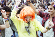 Woman in wig dancing at music festival - CAIF03638