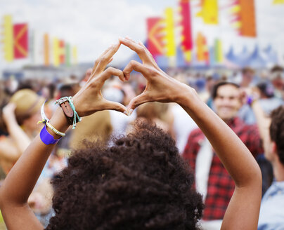 Woman forming heart-shape with hands at music festival - CAIF03641