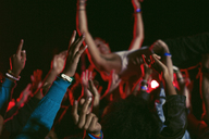 Man crowd surfing at music festival - CAIF03644