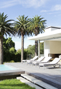 Lounge chairs poolside of modern house - CAIF03704