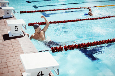 Swimmer celebrating in pool - CAIF03725