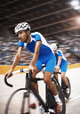 Track cyclists riding in velodrome - CAIF03728