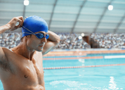 Swimmer adjusting goggles at pool - CAIF03731