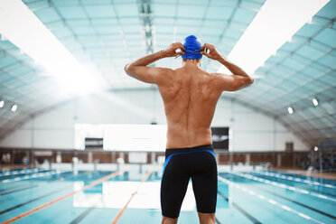 Swimmer adjusting goggles at poolside - CAIF03746