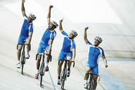 Track cycling team riding in velodrome with arms raised - CAIF03749