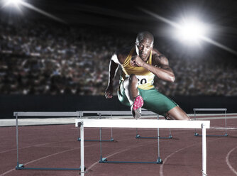 Runner clearing hurdle on track - CAIF03764