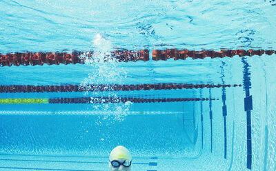 Swimmer smiling underwater in swimming pool - CAIF03770