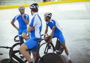 Track cycling team talking in velodrome - CAIF03776